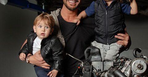 Julio Rocha posa com os filhos em oficina mecânica